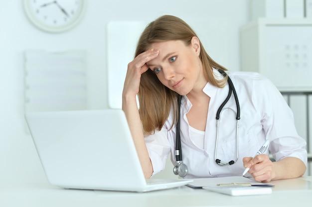 Portret uroczej lekarki z laptopem