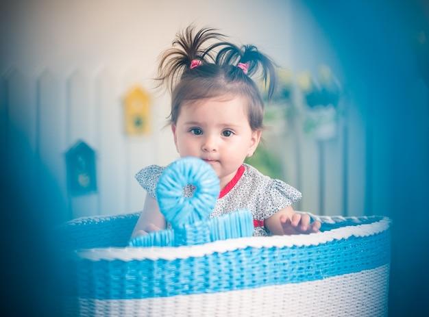 Portret uroczej małej, pięknej dziewczynki siedzącej w dużym koszu na zabawki w swoim przytulnym pokoju dziecięcym.