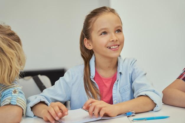 Portret uroczej małej uczennicy, która uśmiecha się i słucha podczas nauki, siedząc w