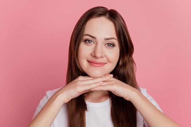 Portret uroczej marzycielskiej uroczej dziewczyny uśmiech wygląda na aparat ręce podbródek na różowym tle