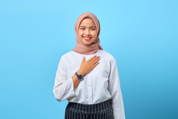 Portret uroczej młodej azjatki, która położyła ręce na piersi, z szacunkiem dumnym na niebieskim tle