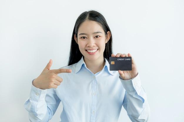 Portret uroczej młodej azjatki, pięknej kobiety z długimi włosami, trzymającej niebieską kartę kredytową, jej oczy błyszczą w aparacie. gotowy do zapłaty za zakupy według przecenionych produktów.