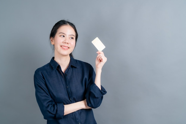 Portret uroczej młodej azjatki pokazującej kartę kredytową z miejscem na kopię