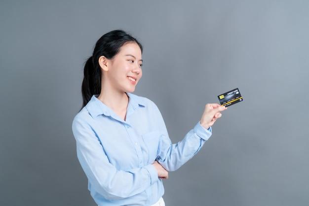 Portret uroczej młodej azjatki w niebieskiej koszuli pokazującej kartę kredytową z miejscem na kopię