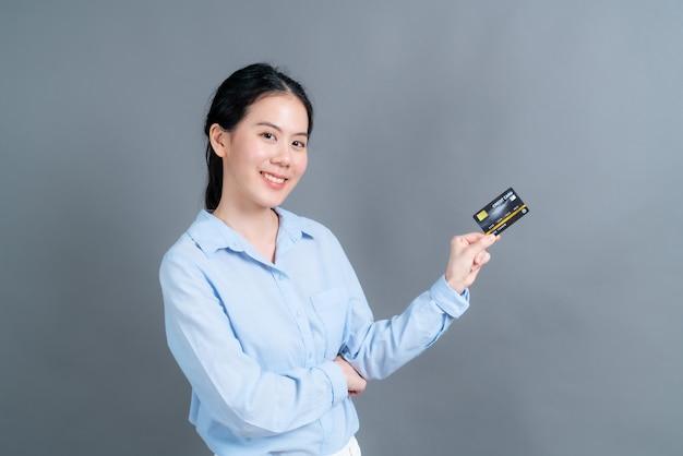 Portret uroczej młodej azjatki w niebieskiej koszuli pokazującej kartę kredytową