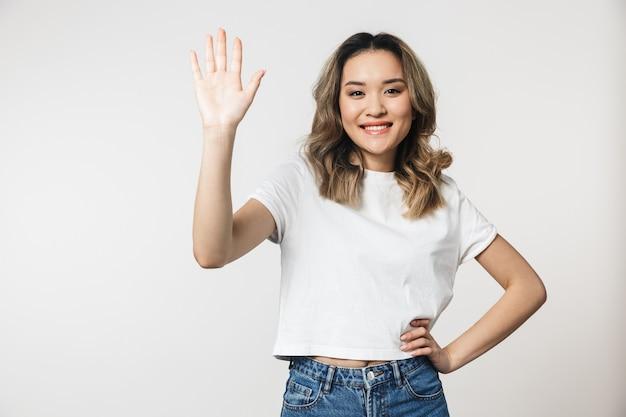 Portret uroczej młodej azjatyckiej kobiety stojącej odizolowanej nad białą ścianą, machającej ręką