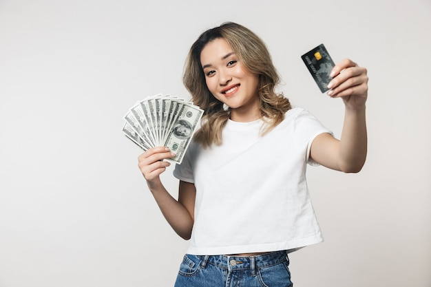 Portret uroczej młodej azjatyckiej kobiety stojącej odizolowanej nad białą ścianą, pokazującej banknoty pieniędzy i plastikową kartę kredytową