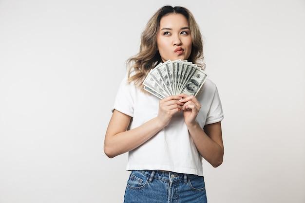 Portret uroczej młodej azjatyckiej kobiety stojącej odizolowanej nad białą ścianą, pokazującej banknoty pieniędzy