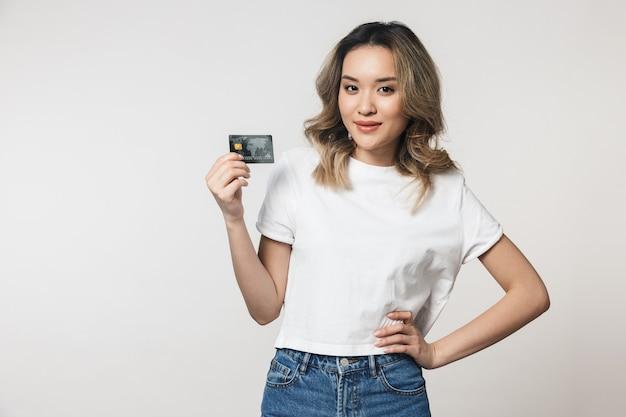 Portret uroczej młodej azjatyckiej kobiety stojącej odizolowanej nad białą ścianą, pokazującej plastikową kartę kredytową