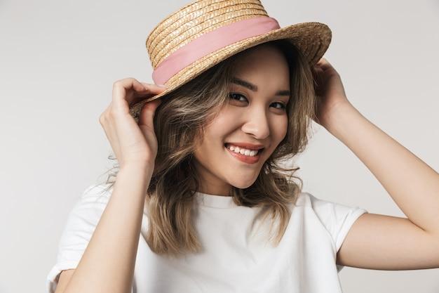 Portret uroczej młodej azjatyckiej kobiety stojącej odizolowanej nad białą ścianą, w letnim kapeluszu, pozującej