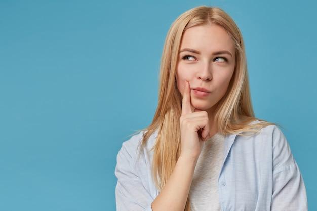Portret uroczej młodej blondynki z długimi włosami, ubrana w niebieską koszulę i szarą koszulkę, pozująca z przebiegłym spojrzeniem, trzymająca palec na twarzy i uśmiechnięta lekko