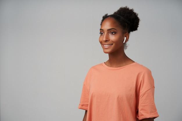 Portret uroczej młodej brunetki ciemnoskórej kobiety ze słuchawkami w uszach, patrząc z radością przed siebie i uśmiechając się lekko, stojąc na szaro