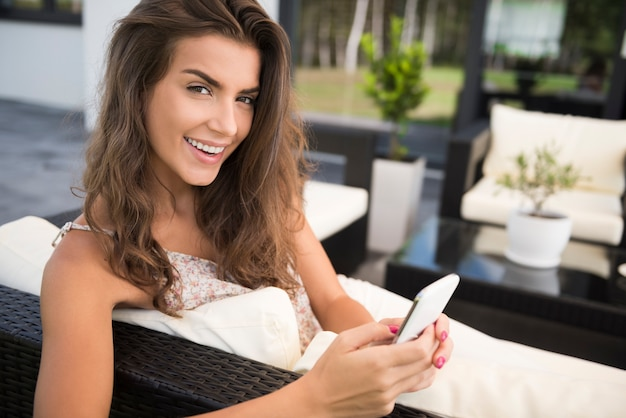 Portret uroczej młodej kobiety na tarasie z smartphone
