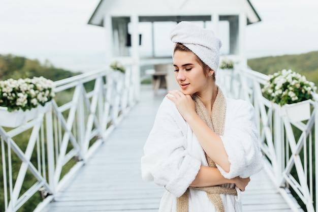 Portret uroczej, młodej kobiety odpoczywającej w górach, przebywającej na tarasie willi i pozującej, ubranej w białą szatę.