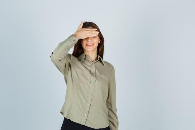 Portret uroczej młodej kobiety trzymającej rękę na oczach w koszuli i patrzącej na wesoły widok z przodu