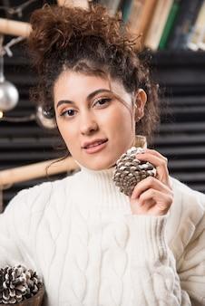 Portret uroczej młodej kobiety trzymającej szyszki w dłoniach