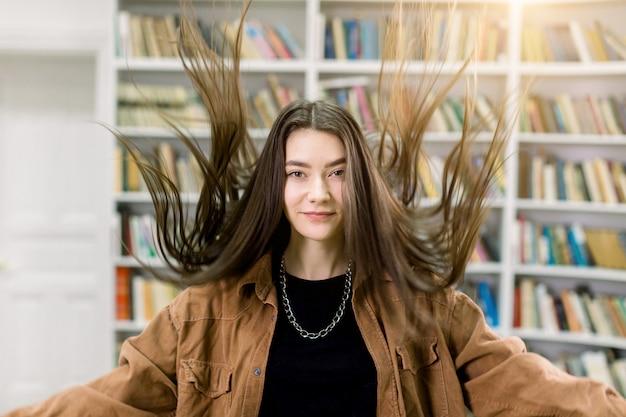 Portret uroczej młodej kobiety w brązowej koszuli z długimi prostymi włosami, które pozują na czytelni biblioteki, podrzucając włosy