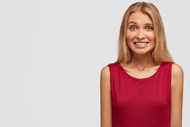 Portret uroczej młodej kobiety w czerwonej koszulce, chichocze, ma zębaty uśmiech, pokazuje białe idealne zęby