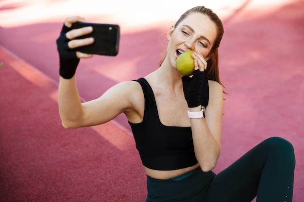 Portret uroczej młodej kobiety w dresie, biorąc selfie na smartfonie i jedząc jabłko, siedząc na boisku sportowym podczas treningu w zielonym parku