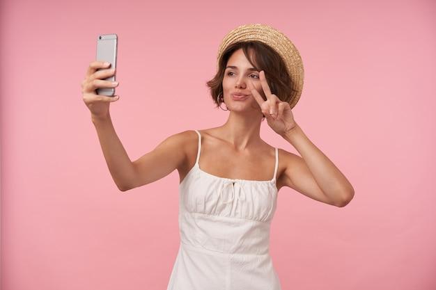 Portret uroczej młodej kobiety z krótkimi brązowymi włosami, ubrana w białą letnią sukienkę i słomkowy kapelusz, podnosząca rękę z gestem pokoju podczas robienia selfie ze smartfonem, na białym tle