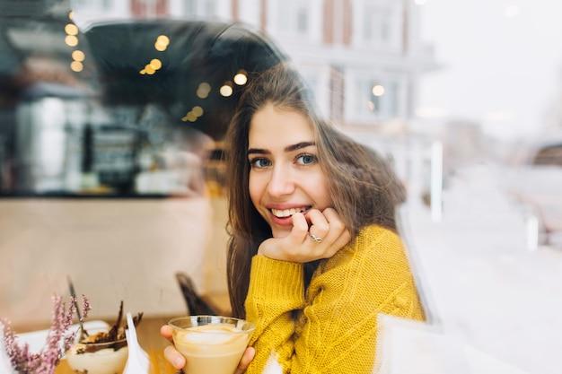 Portret uroczej młodej kobiety z przyjaznym uśmiechem, długie brunetki, uśmiechając się w oknie kawiarni w okresie zimowym. prawdziwie pozytywne emocje, czas wolny, picie kawy, chłodzenie w chłodne dni.