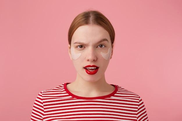 Portret uroczej młodej niezadowolonej rudowłosej pani z czerwonymi ustami i łatami pod oczami, ubrana w czerwoną koszulkę w paski, stoi z szeroko otwartymi ustami i uniesionymi brwiami.
