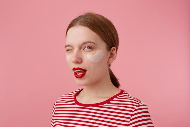 Portret uroczej młodej rudowłosej kobiety z czerwonymi ustami i łatami pod oczami, ubrana w czerwoną koszulkę w paski, patrzy i mruga, pokazuje język, stoi.