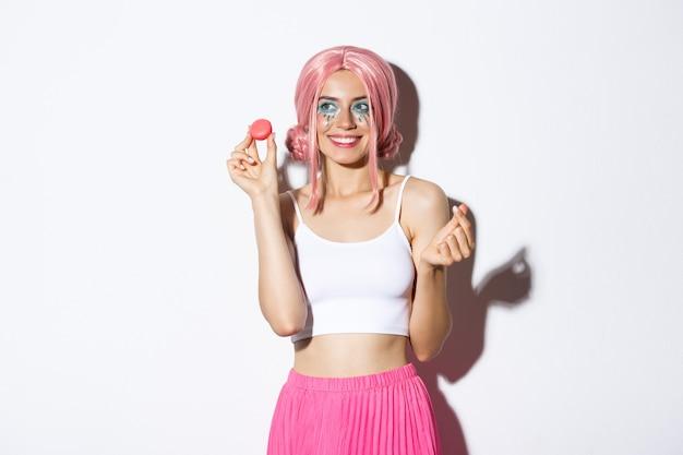 Portret uroczej modelki jedzącej makaroniki i uśmiechającej się, ubranej w różową perukę i strój na imprezę, stojącej na białym tle