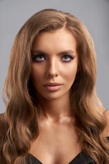 Portret uroczej modelki z jasnym makijażem i modną fryzurą. pojedynczo na szarym ścianie studio. pojęcie stylu i piękna.