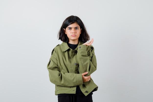 Portret uroczej nastolatki rozkładającej dłoń na bok, dąsając się w zielonej kurtce i patrząc na zdziwionego widok z przodu