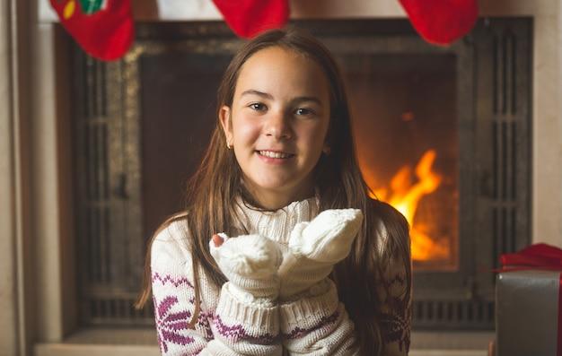 Portret uroczej nastoletniej dziewczyny siedzącej przy kominku i dmuchającej śniegiem z rąk