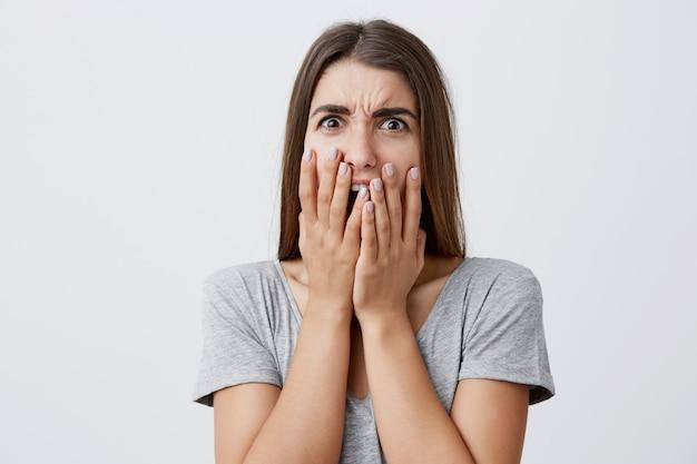 Portret uroczej nieszczęśliwej pięknej brunetki kaukaskiej studenckiej dziewczyny z długą fryzurą w stylowej szarej koszuli ubraniowej usta rękami z wyrazem twarzy zszokowanej i obrzydzonej