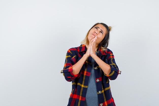 Portret uroczej pani pokazującej splecione dłonie w błagalnym geście, patrzącą w górę w kraciastą koszulę i smutnym widokiem z przodu
