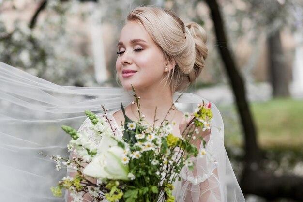 Portret uroczej panny młodej blondynki ze świeżym bukietem kwiatów w parku