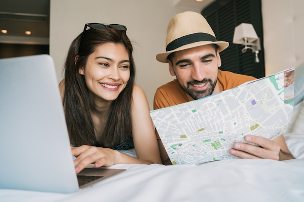Portret uroczej pary organizującej wyjazd z laptopem w pokoju hotelowym.