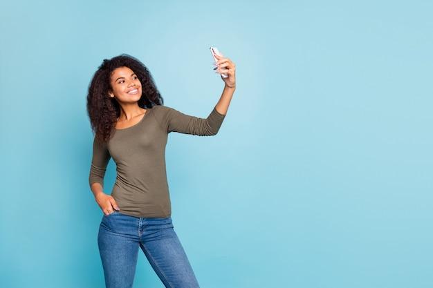 Portret uroczej, pozytywnej, wesołej afroamerykańskiej dziewczyny, która ma wolny czas w podróży, biorąc selfie wideo na swoim blogu, nosić dżinsy w stylu casual, strój dżinsowy na białym tle na niebieskiej ścianie