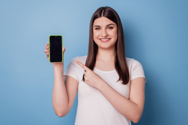 Portret uroczej promotorki, trzymającej smartfon z ekranem dotykowym, pokazującym pustą przestrzeń na niebieskim tle