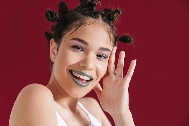 Portret uroczej punkowej dziewczyny z dziwaczną fryzurą i ciemną szminką uśmiecha się do kamery odizolowanej na czerwonej ścianie