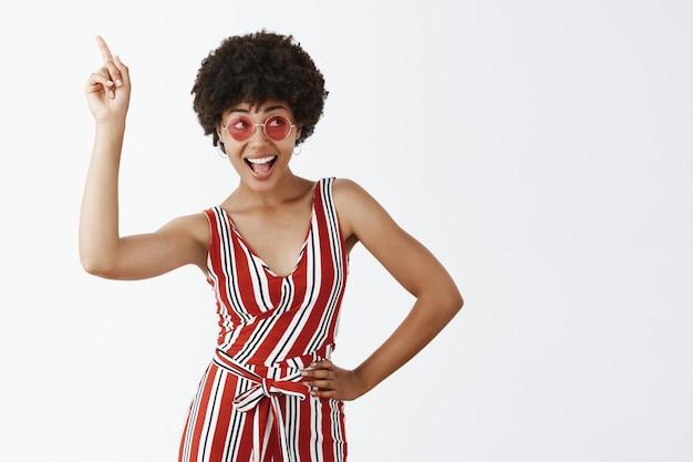 Portret uroczej radosnej dziewczyny w pasiastych stylowych kombinezonach i okrągłych okularach przeciwsłonecznych podnosząc palec wskazujący, wskazując w górę i robiąc dyskotekę, poruszając się, uśmiechając się szeroko i patrząc w prawo
