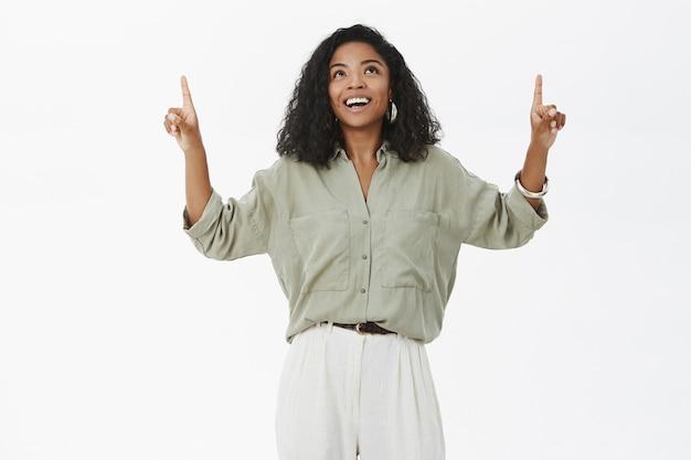 Portret uroczej, radosnej i rozmarzonej ciemnoskórej kobiety z kręconymi fryzurami, podnosząc ręce, wskazując i patrząc w górę