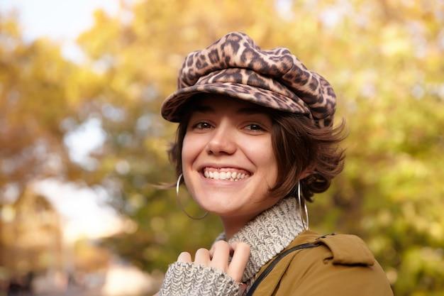 Portret uroczej radosnej młodej brunetki w czapce z nadrukiem lamparta, stojąc nad rozmytym parkiem, patrząc szczęśliwie z szerokim, czarującym uśmiechem