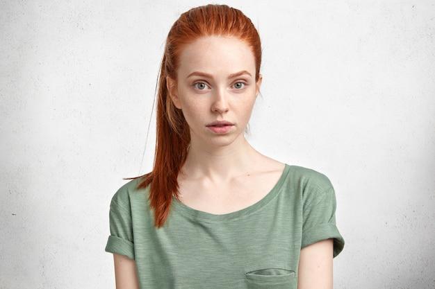 Portret uroczej rudej kobiety o piegowatej skórze i tajemniczym wyglądzie, ubrana w casualową koszulkę, odizolowaną na białym betonie