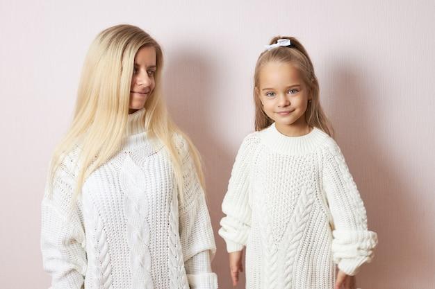 Portret uroczej ślicznej dziewczynki ubierającej dzianinowy sweter i wstążkę we włosach, uśmiechając się, spędzając miło czas z troskliwą kochającą matką, która patrzy na córkę z miłością i czułością