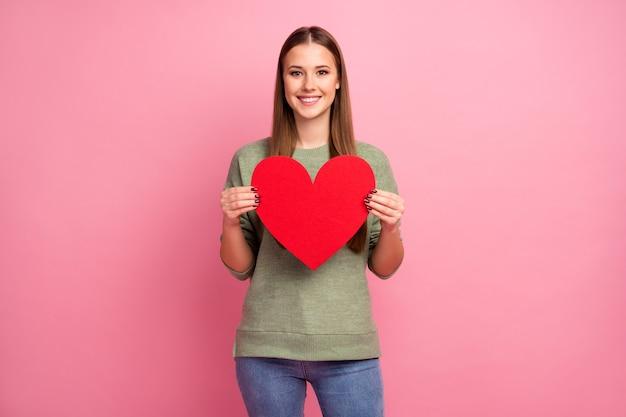 Portret uroczej słodkiej dziewczyny trzymają czerwone wielkie serce karty papieru