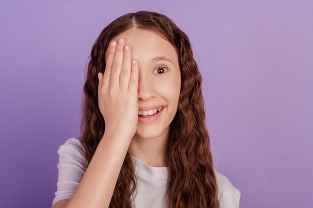 Portret uroczej słodkiej małej damy dłoni blisko pół twarzy spojrzenie na aparat oko na fioletowym tle