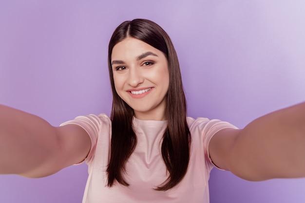 Portret uroczej słodkiej pozytywnej damy trzyma aparat strzelać selfie błyszczący uśmiech na fioletowym tle