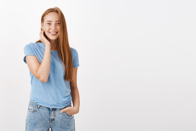 Portret uroczej szczęśliwej, entuzjastycznej kobiety z rudymi włosami i piegami, uśmiechnięta przyjazna, dotykająca szyja i trzymająca rękę w kieszeni, nieśmiała i nieśmiała rozmawiająca z uroczym baristą podczas zamawiania kawy