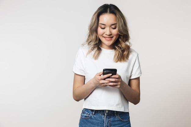 Portret uroczej, szczęśliwej młodej azjatyckiej kobiety stojącej na białym tle nad białą ścianą, przy użyciu telefonu komórkowego
