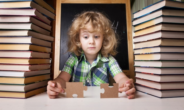 Portret uroczej uczennicy myślącej siedząc ze stosem książek przy stole