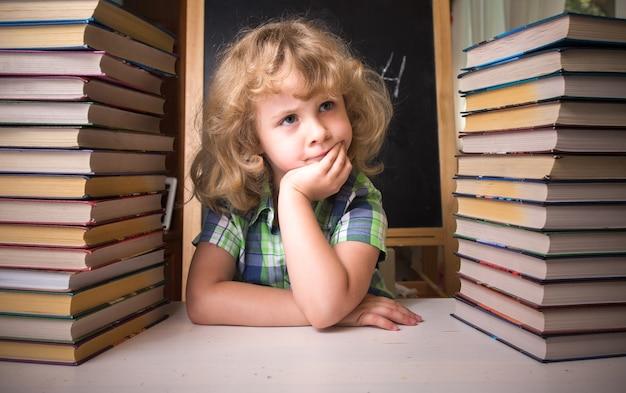 Portret uroczej uczennicy myślącej siedząc ze stosem książek